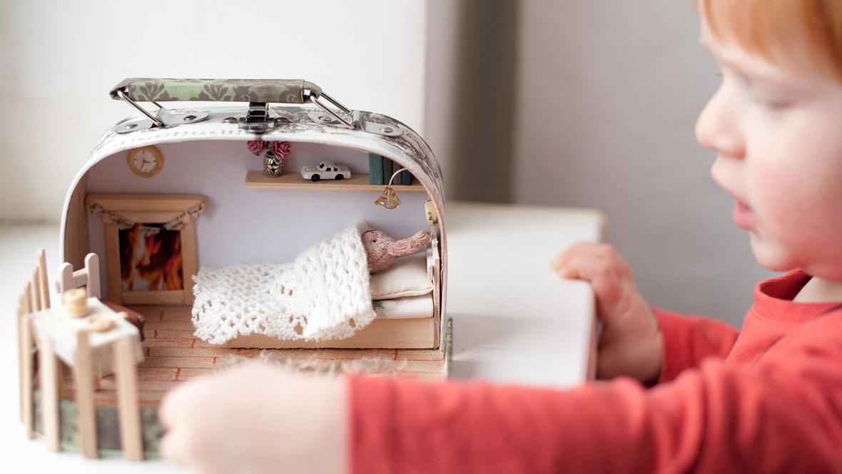Kleiner Junge spielt mit Puppenhaus