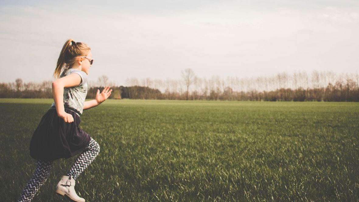 Mädchen rennt über Wiese