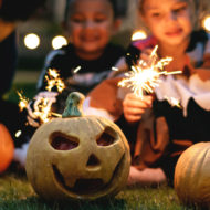 Halloweenparty: Kinder sitzen vor Kürbis