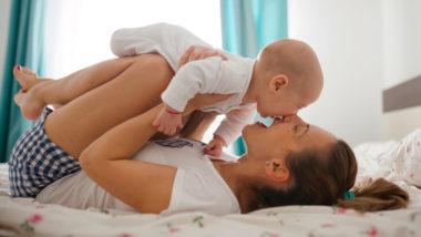 Mutter spiel mit Baby auf Bett