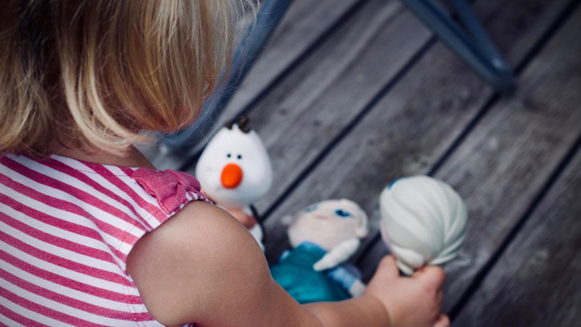 Blondes Kind spielt mit Puppen.