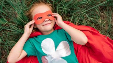 Mädchen im Superhelden-Kostüm liegt im Gras.
