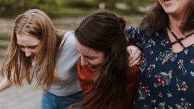 Drei Frauen liegen sich in den Armen und lachen