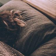 Frau liegt mit Schwangerschaftsübelkeit in einem Bett