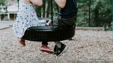 Zwei Kinder spielen auf der Schaukel