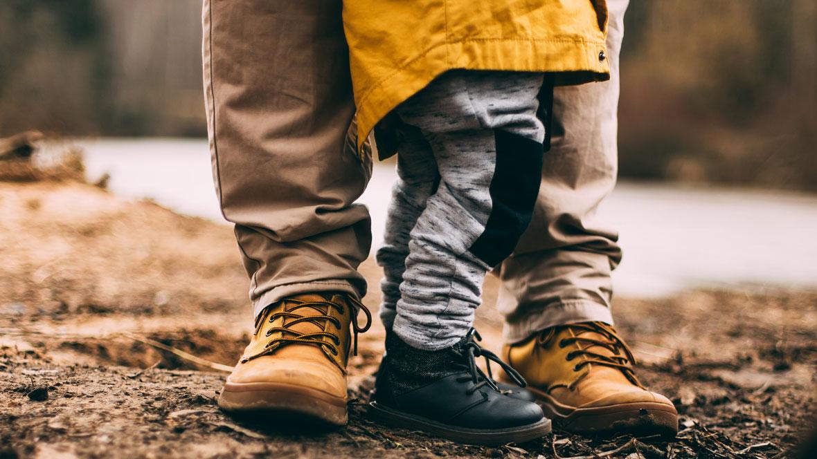 Vater und Kind spazieren im Wald