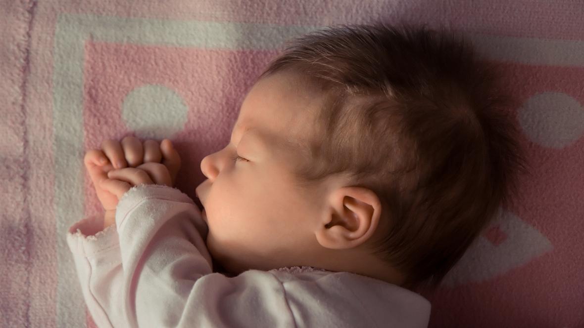 Baby liegt auf rosa Decke