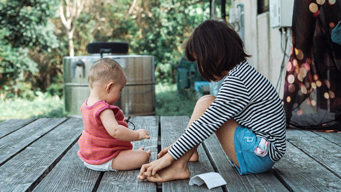 Zwei Kinder sitzen auf Holzboden.