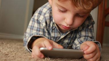 Kind liegt am Boden und schaut auf ein Handy