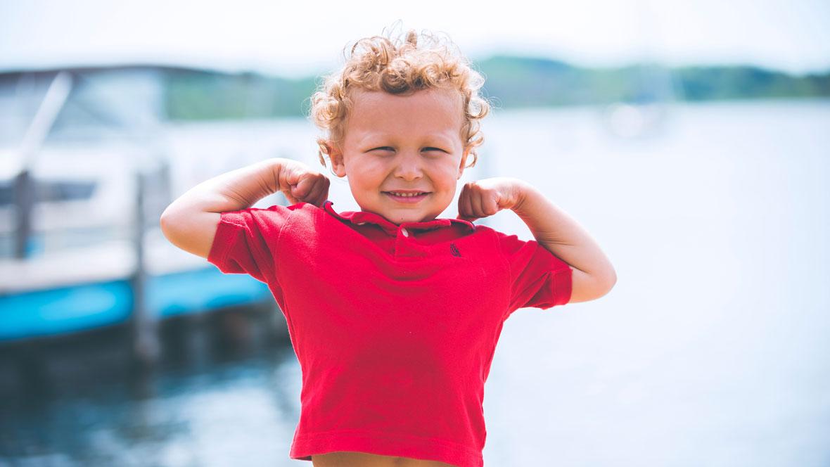 Junge im roten Shirt steht am Wasser