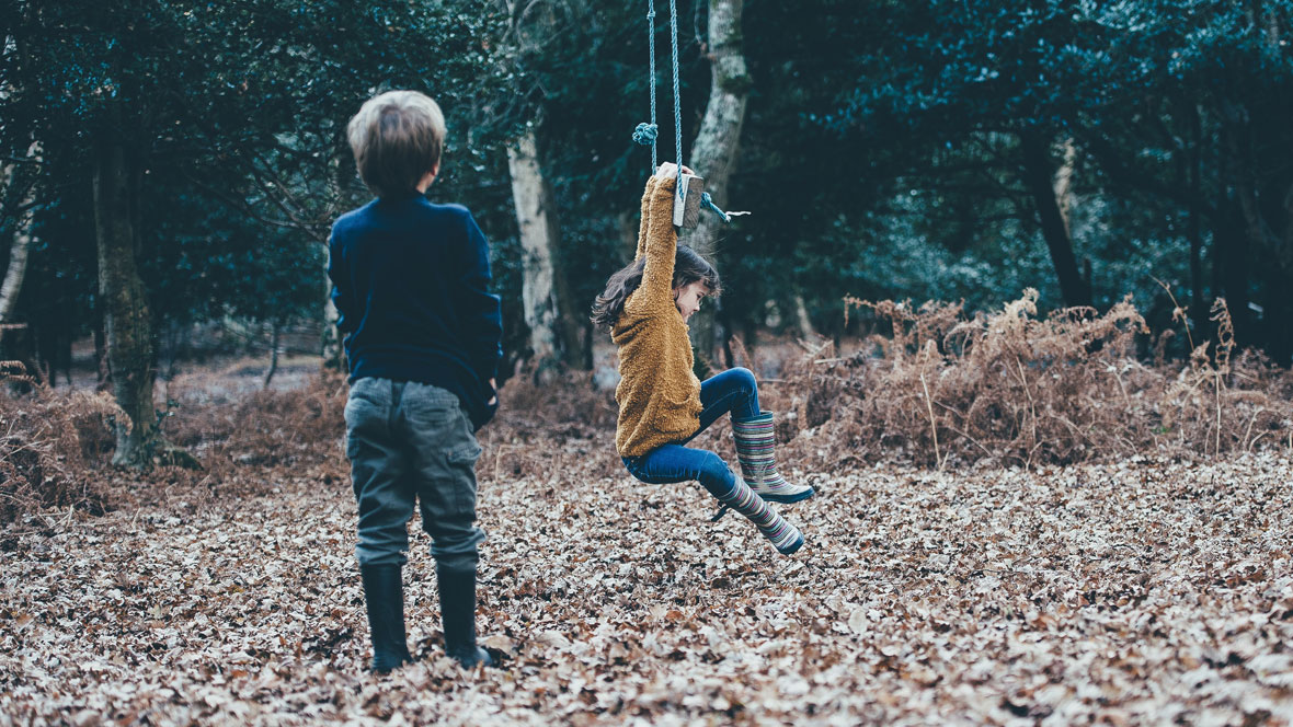 Junge und Mädchen spielen zusammen im Wald