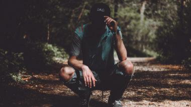 Vater mit Mütze sitzt im Wald