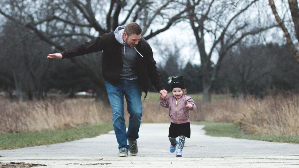 Vater und Tochter laufen zusammen im Park