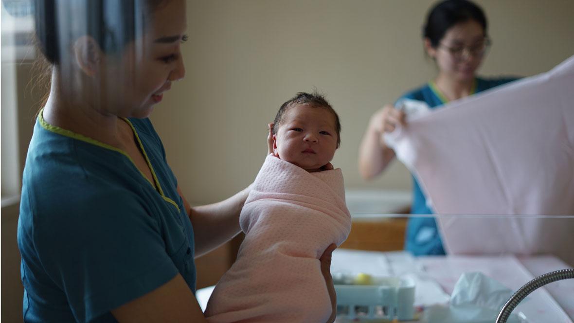 Hebamme hält Neugeborenes