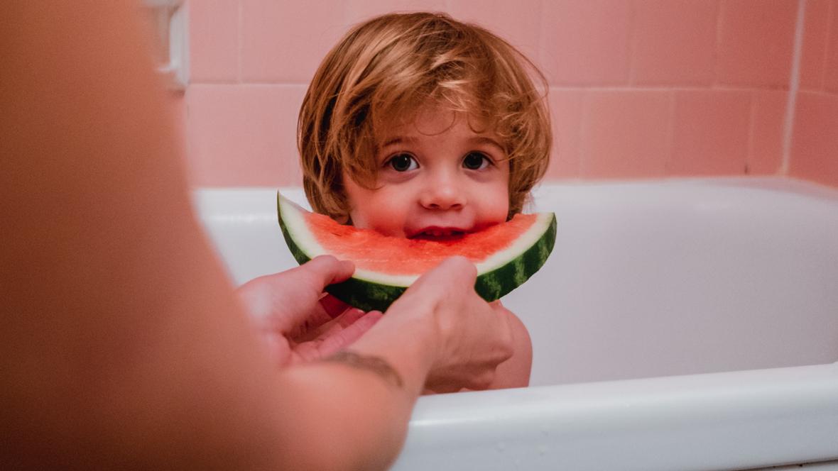 Kind sitzt in einer Badewanne und isst eine Melone