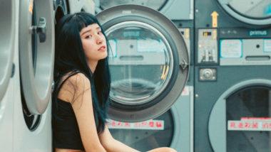 Frau sitzt vor einer Waschmaschine