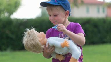 Junge spielt mit einer Puppe