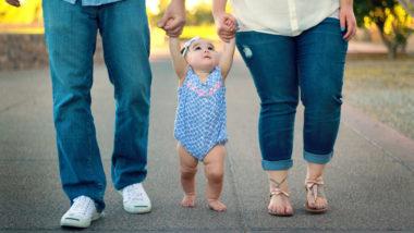 Baby geht an den Händen der Eltern