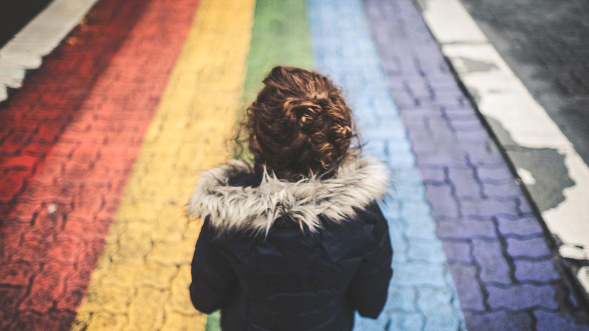 Kind geht auf einer Straße mit einem Regenbogen