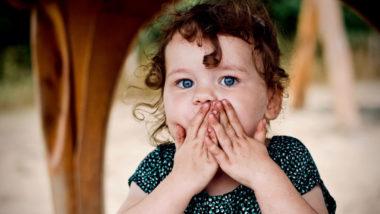 Mädchen hält sich die Hände vor den Mund