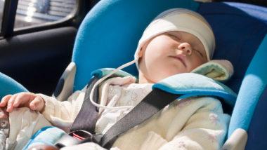 Kind schläft in Kindersitz im Auto