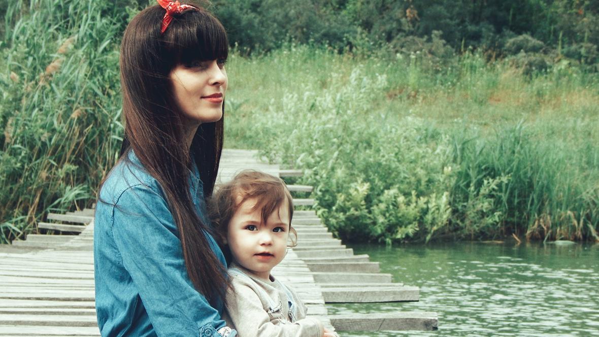 Mutter sitzt mit Kind auf einem Steg