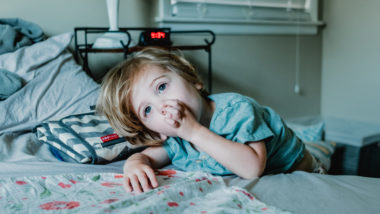 Kind liegt im Bett