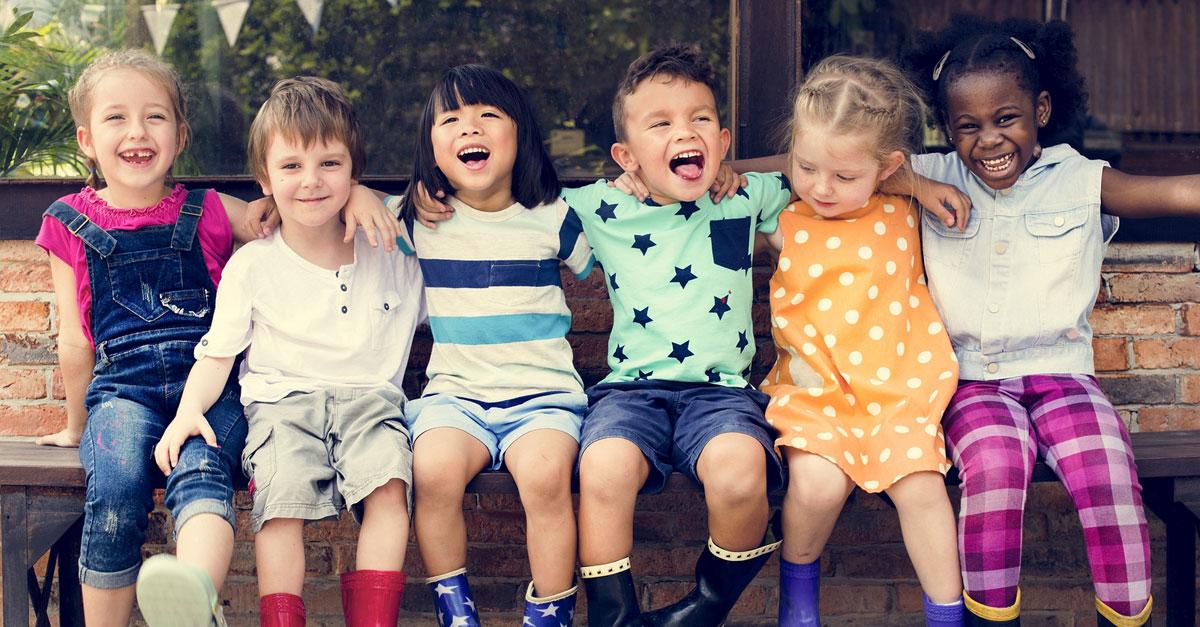 Kinder sitzen auf einer Bank und lachen