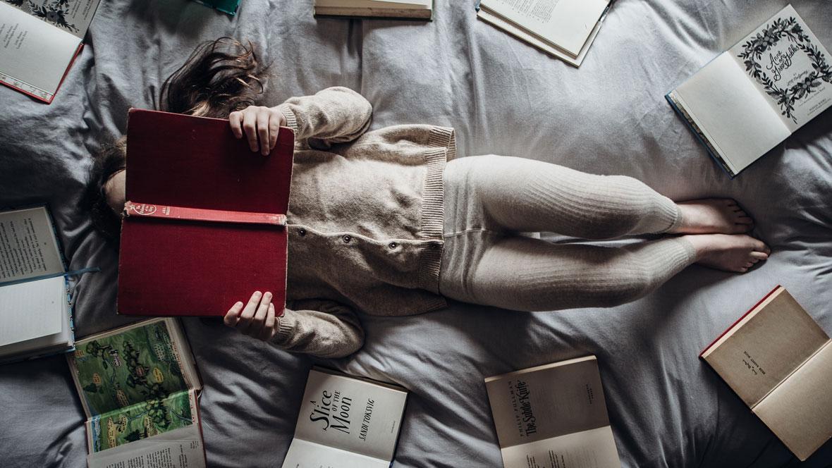 Kind liest ein Buch auf einem Bett