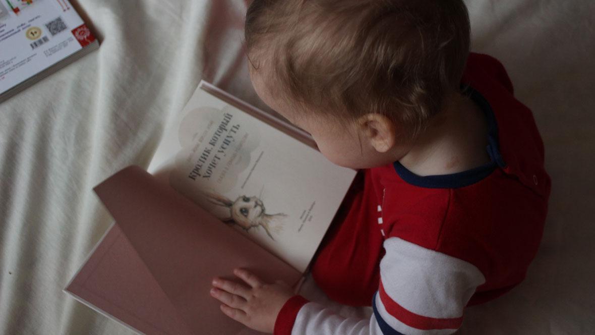 Baby blättert in einem Buch