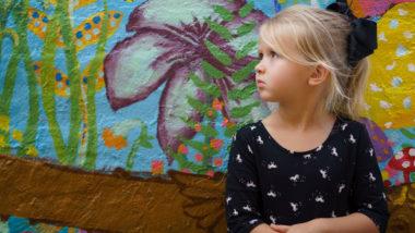 Blondes Mädchen steht vor einer bunten Wand
