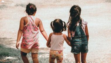 Drei Mädchen laufen eine Wiese entlang; Kinderspiele für 2- und 3-Jährige sind vor allem eines - lustig!