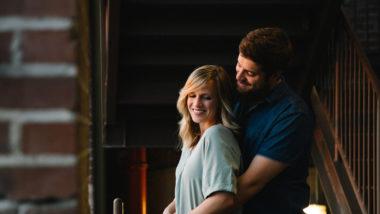 Paar umarmt sich vor einer Backsteinwand