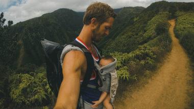 Vater trägt Kind in einer Babytrage vor dem Bauch
