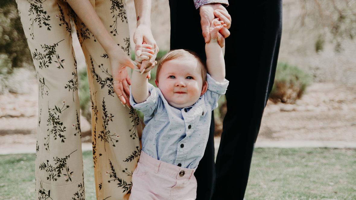 Baby läuft an den Händen seiner Eltern