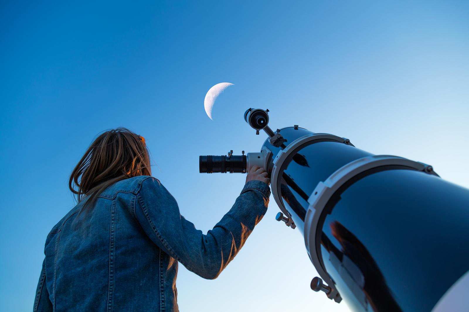 Frau schaut durch ein Fernrohr in die Sterne