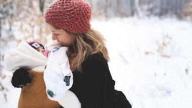 Mutter trägt ihr Baby in Babytrage durch den Schnee