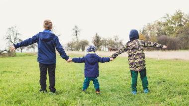 Drei Kinder halten sich auf einer Wiese an den Händen