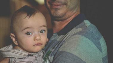 Vater hält Baby auf dem Arm