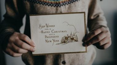 Kind hält Karte mit Weihnachtssprüchen