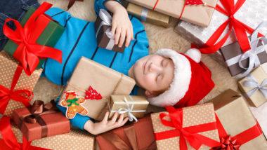 Kind liegt inmitten von vielen Geschenken