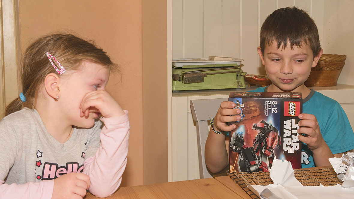Junge packt ein Geschenk aus und seine Schwester schaut ihm dabei zu.