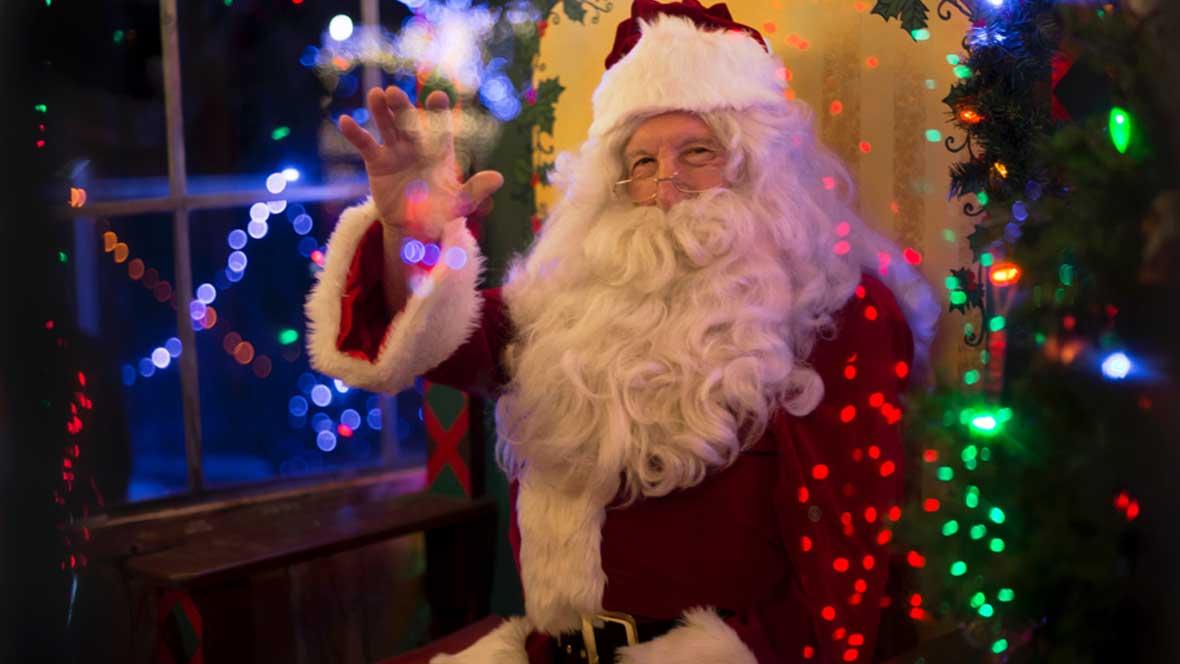 Weihnachtsmann sitzt vor bunten Lichtern