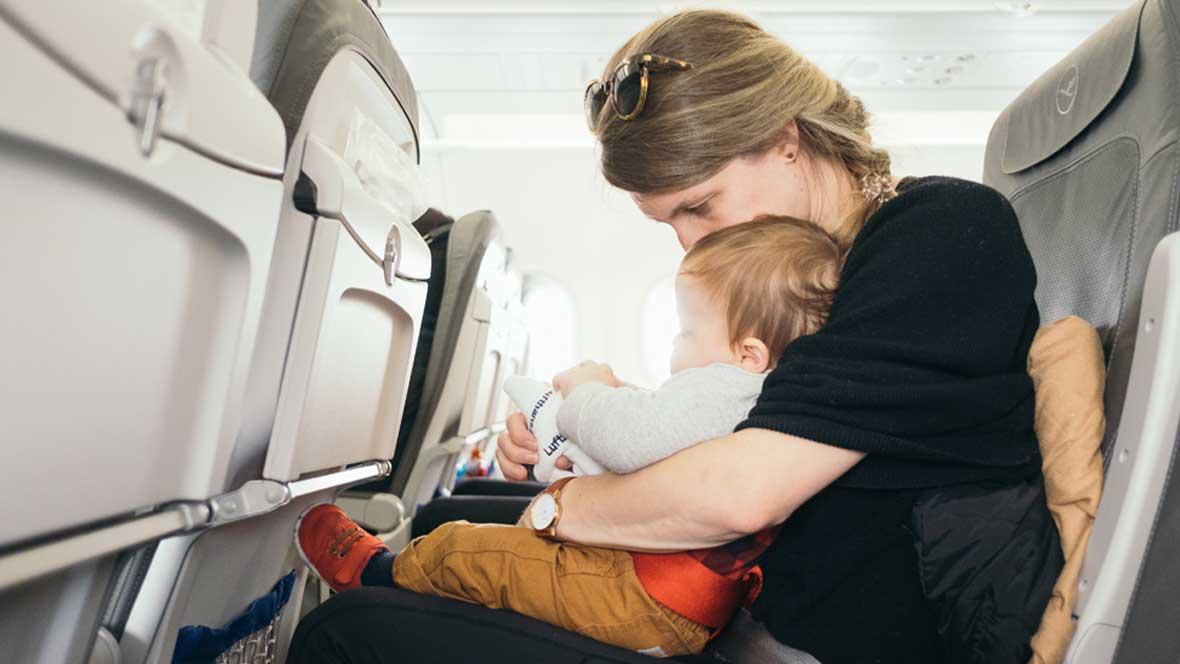 Frau sitzt mit ihrem Baby im Flugzeug