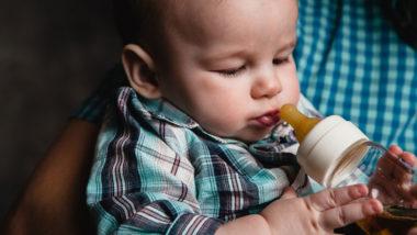 Baby trinkt Tee aus der Flasche