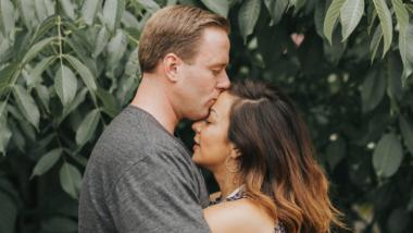 Mann küsst seine Frau auf die Stirn