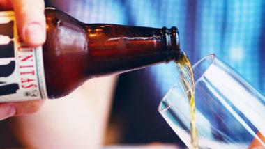 Bier wird aus einer Flasche in ein Glas geschenkt