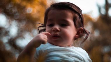 Kleines Mädchen schaut sich auf den Finger