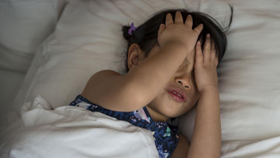 Kind hält sich den Kopf vor Schmerzen