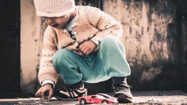 Kleines Mädchen spielt auf der Straße mit einem Auto